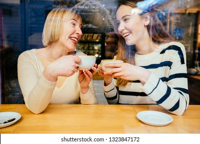 View through the window of young beautiful blonde girl talking to her mom an interesting secret, they sit at cafe, happy and laugh. Bonding, different generationsconnect, family concept.
