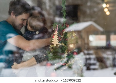 View through a window of a young couple with a baby standing next to a decorated Christmas tree in a loving hug with snowy winter nature reflecting in the glass.