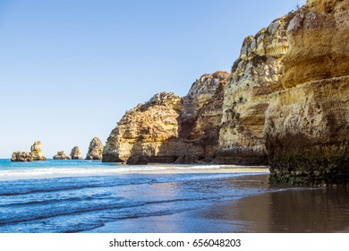 A view of the tide coming in from the rocky beach in Lagos, Portugal during sunset