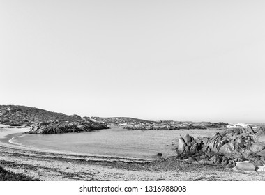 A view of Tietiesbaai Caravan Park in the Cape Columbine Nature Reserve near Paternoster. An ablution building and a motorhome are visible. Monochrome