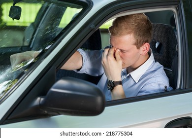 View of tired businessman driving a car