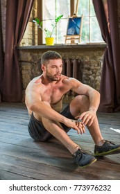 View of tired man sitting on floor after doing sport exercises. Young guy with naked torso training his body at home.