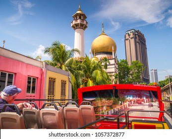 View from the top of a bus in Singapore, Kampong district.  Looking up at the iconic gold dome of Masjid Sultan also know as Sultan Mosque. The street can be seen through the front bus window.