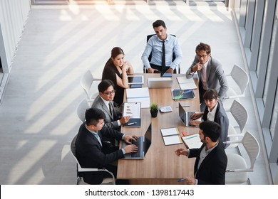 view from the top of caucasian lecturer giving public presentation with company business graph result on white board in meeting room and multiethnic business people are paying attention