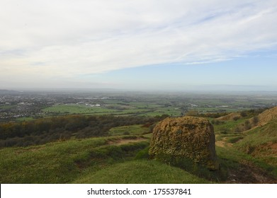 View from the top of Cleeve Hill in the Cotswolds towards the town of Cheltenham and its horse race course in Gloucestershire with rock in foreground