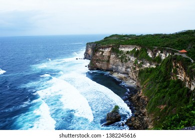 the view from the top of the cliff with green tree surrounded by the beach, with waves marching against the cliffs. beach in Uluwatu, Bali, Indonesia.