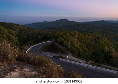 View from the top of the cliff, tree tops touched by the sun showing a golden glow and Hua Sua Viewpoint in the background, Doi Inthanon, Chiangmai, Thailand