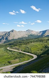The view from the top of Cottonwood Pass, along the Continental Divide near Buena Vista, Colorado showcases beautiful blue sky, rugged mountain peaks, green valleys filled with pine forests.