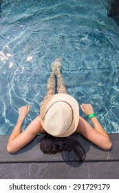 View from the top of a girl in a hat relaxing in the swimming pool
