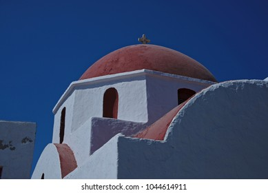 View of the top of a Greek Orthodox church. The building has a red roof and white walls.