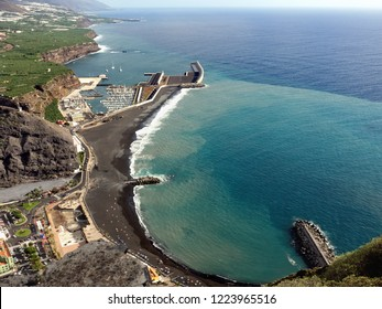 """View from the top of the harbor and the village """"Puerto de Tazacorte"""" on the Canary Island """"La Palma"""". Visible are the black large lava sand beach, the marina and the mouth of the large barranco."""