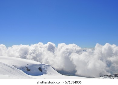 View from top of high snow-capped mountain landscape with blue sky and clouds
