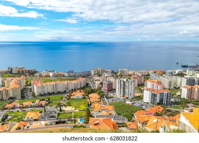 View from the top of the hill to the city in Madeira, Portugal with the sea on the background during a cloudy day