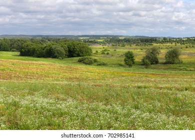 View from the top of a hill to a wide green fields.