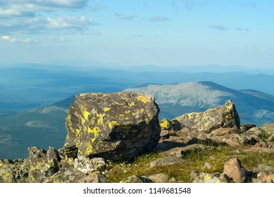 view from the top of Mount Konzhakovskiy Kamen - section of mountain tundra with lichen-covered rocks and a view of the wooded mountains to the horizon