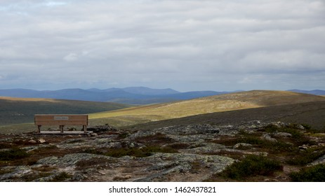 """View from top of Kiilopää mountain in Lapland, Finland on July with a bench with words """"Ulkona. Perillä."""" meaning outdoods, arrived."""