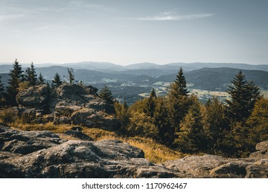 View from top of a mountain in the valley with clouds on the sky and mountains on the background and stones and trees in front of in the bavarian forest