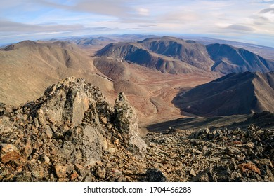 View from the top of the mountain to the valley and mountains. Travel in the wild. Hiking, Trekking and climbing in the Arctic. Autumn landscape. Golden Ridge, Chukotka, Siberia, Far East of Russia.