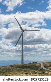 View of a top mountains landscape with a wind turbine, cloudy sky as background...
