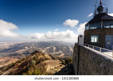 View from top of Mt Diablo observation tower showing cloud shadowed arid summer landscape of hills and ridges in Park