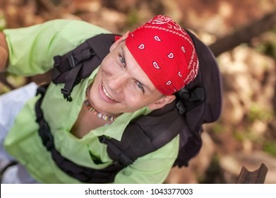 View from top on young man with green shirt and red bandana looking up and smiling, wearing backpack.