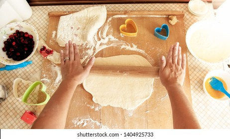 View from top on young woman making dough and rolling it with wooden rolling pin on kitchen counterboard