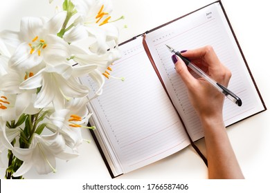 The view from the top. Open journal, black pen, bouquet of Lily flowers with hands on a white background