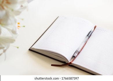 The view from the top. Open journal, a bouquet of lilies on a white background