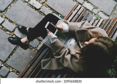 View from the top photo of a female reading messages on her smartphone while sitting on a bench in a city garden. Hipster girl chatting with friends by mobile phone with empty display for your content