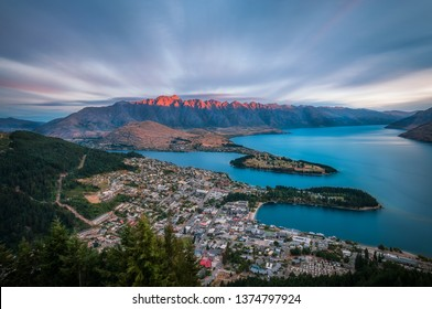 View from the top of Queenstown Skyline in New Zealand, with an amazing sunset on the spectacular Remarkables Mountain in the background washed in red light, raising over the waters of lake Wakatipu.