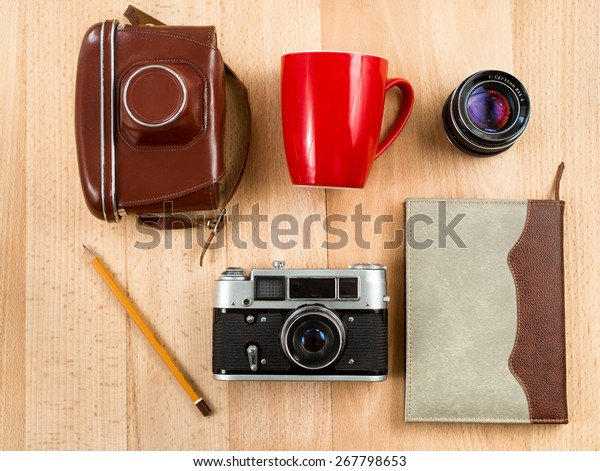 View from top of retro journalist workspace with camera, lens, notebook, pencil and cup