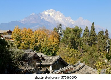 View from the top to roofs of The Old Town of Lijiang with mountain in the background, China. Lijiang was inscribed on the UNESCO World Heritage List in 1997.
