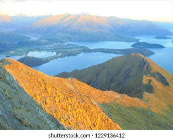 view from the top of Roys Peak during sunrise, rays of light slowly covering mountain range near Wanaka nad lake Wanaka, charming town in Otago region, New Zealand