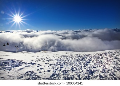 View from Top of Ski Resort Mountain Peak above the Clouds in France with Sun Flare
