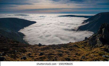 View from the top of Sniezka mountain. Autumn landscape, a lot of fog. Mist over the tops of mountains. Karkonosze mountains. Poland