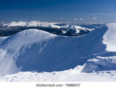 View from the top of the snow-capped mountain range. Ukraine, Dragobrat ski resort, Carpathian mountains.
