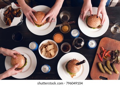 The view from the top of the table, on which are the plates with burgers, cans with alcoholic and non-alcoholic drinks. concept of a party with burgers.