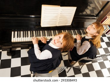 View from top of two girls in uniforms playing piano together with notes during lesson