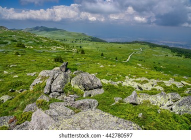 View from the top of Vitosha mountain in Sofia, Bulgaria - with rocky foreground, green meadows, tourist path in the distance and the city of Sofia in the far background. Altitude - 2000 m / 6560 ft