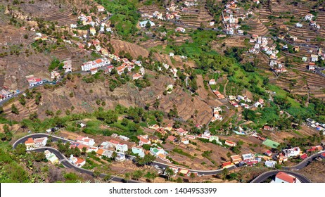 """View from the top of the wide valley, the """"Valle Gran Rey"""" the Valley of the Kings, on the Canary Island of La Gomera. A road winds through the landscape in many loops,"""