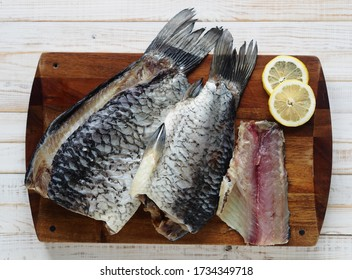 The view from the top.Fish background. Carcasses of freshly salted Russian river fish, ready to eat, on the kitchen cutting Board on a white wooden table.
