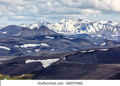 View of tops of mountains under a cloudy sky in Iceland