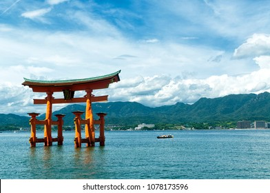 View of the torii (gate) of Itsukushima Shrine at high tide floating in the water of the island of Miyajima, Hiroshima Prefecture, Japan. Unesco World Heritage Site Shrine Shinto complex