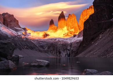 View of Torres del Paine from the base of the main peaks, below you can see the tranquility of its lake. The sunrise overwhelm the peaks. You can also see a sky full of clouds during autumn in Patagon