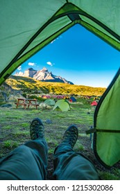 View of Torres del Paine National Park, its forests and mountains and hiking boots of hiker in the tent, at Autumn, Patagonia, Chile