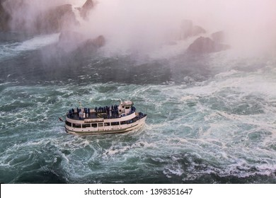 View of tourist boat on rumbling waves of Niagara falls. Beautiful backgrounds. Tourism concept.