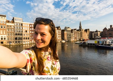 View of a tourist girl on sunset at the Damrak square in Amsterdam