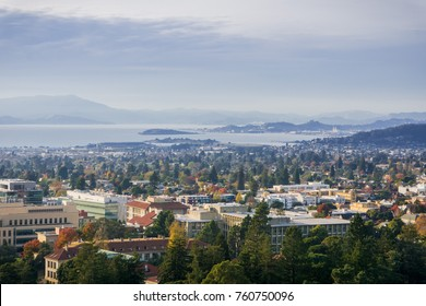 View towards Berkeley and Richmond on a sunny but hazy autumn day; University of California campus buildings in the foreground, San Francisco bay area, California