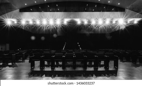 View towards empty audience seats at empty stage in generic acting theatre before performance. Strong deliberate spotlights with light flares. Monochrome