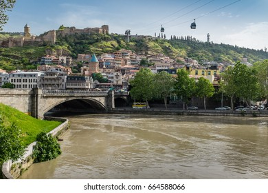 View towards the Old Town district of Tbilisi, in Georgia, Eastern Europe showing the Mtkvari River, Metekhi Bridge, Narikala Fortress and the aerial tramway cable cars.